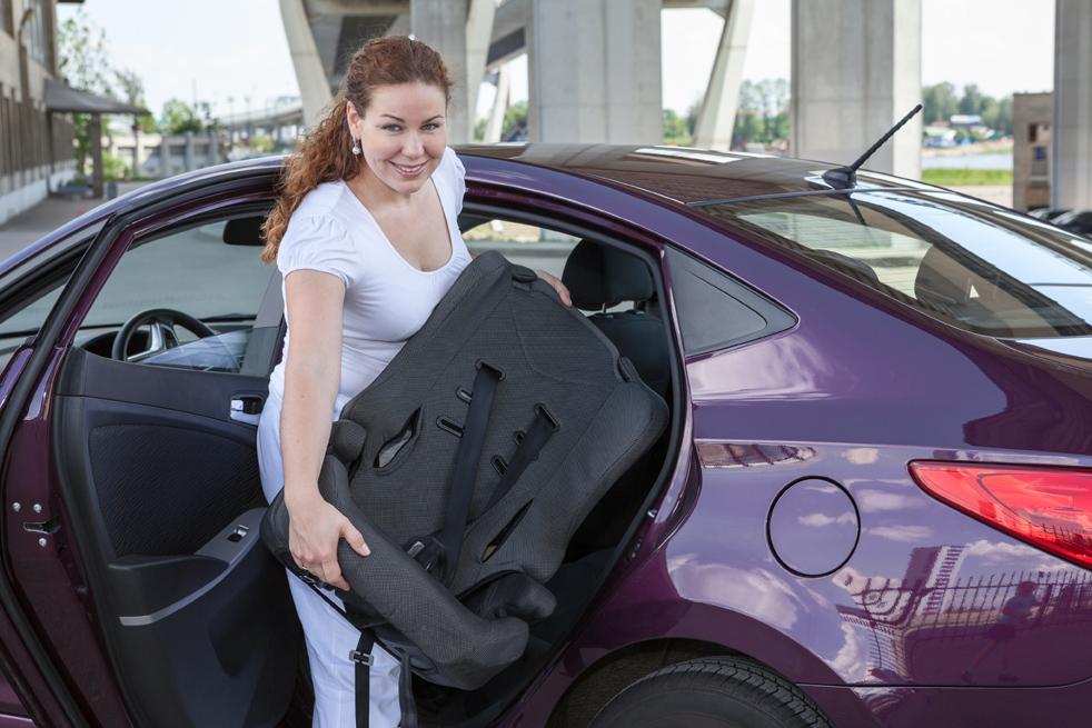 Frau hält Kindersitz vor der geöffneten Autotür in der Hand